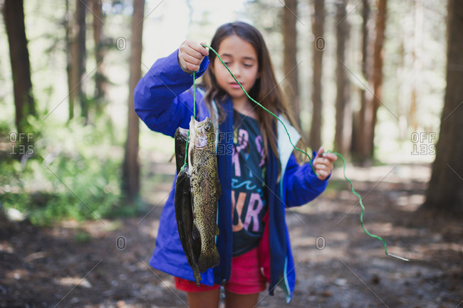 Girl in woods holding up fish