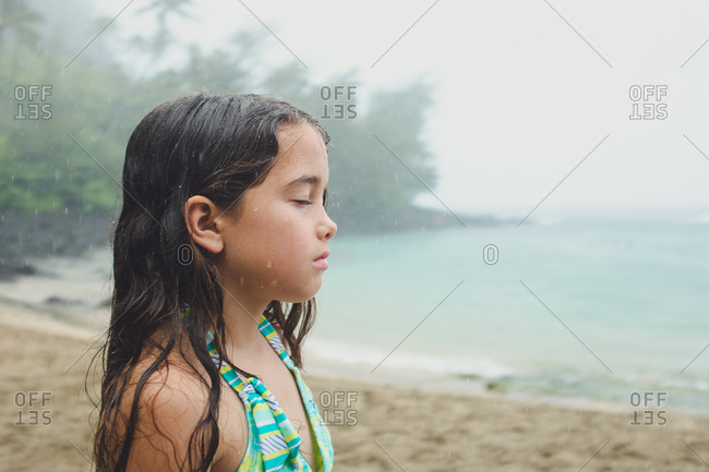 Girl with eyes closed in coastal rain