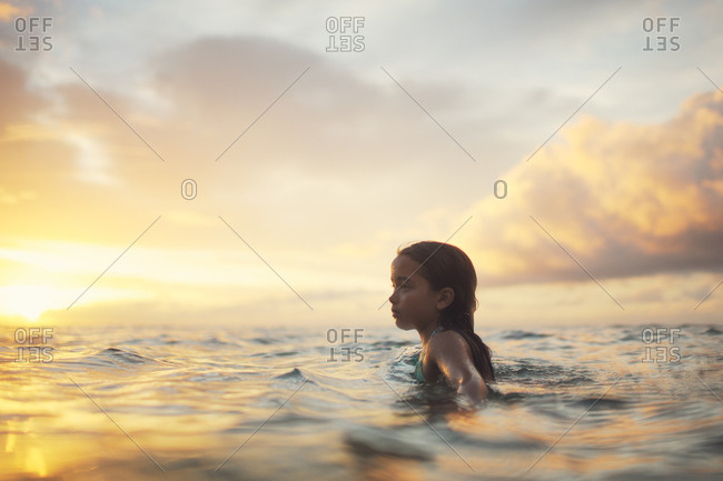 Girl standing in the ocean at dusk