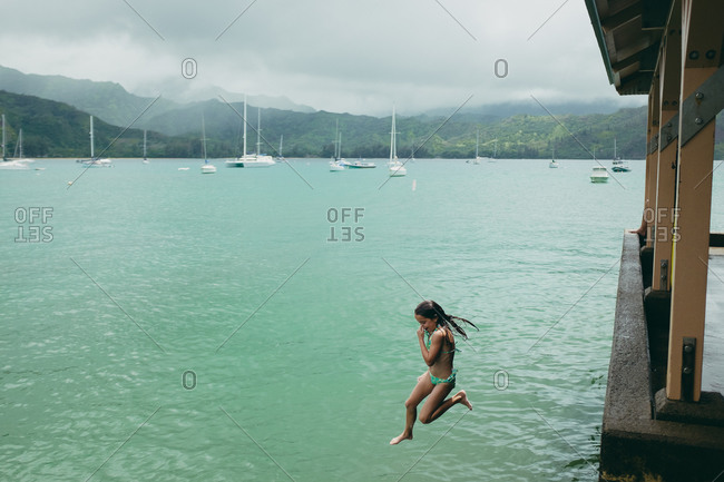 Girl leaping off structure into sea