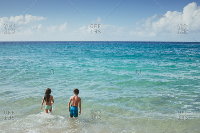 Boy and girl wading in still sea