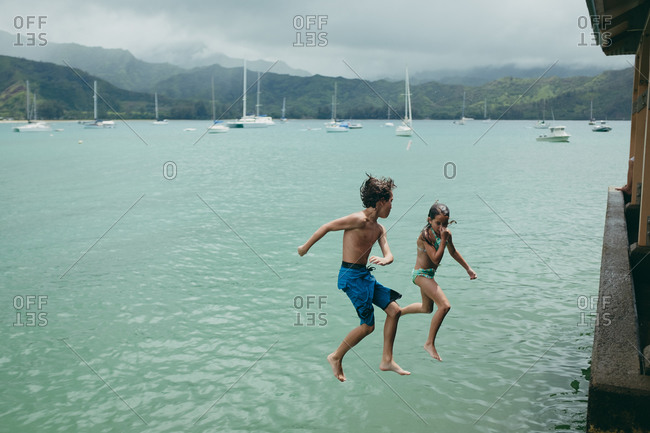 Kids leaping off structure into ocean