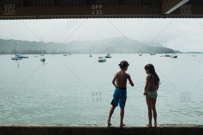 Kids standing on wall overlooking sea