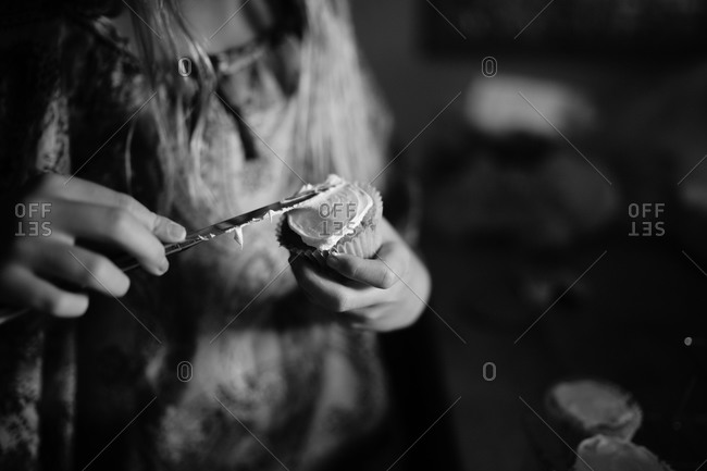 Woman spreading frosting on cupcake