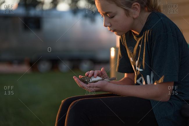 Girl cupping dead bird in hands
