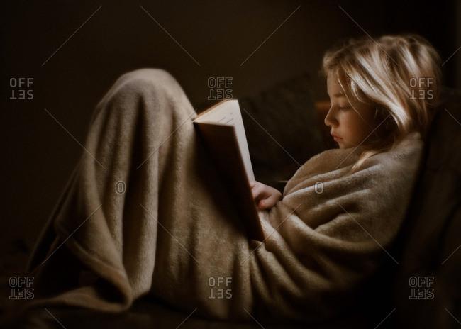 Girl bundled in blanket reading