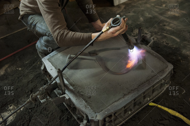 A person making cast iron by hand