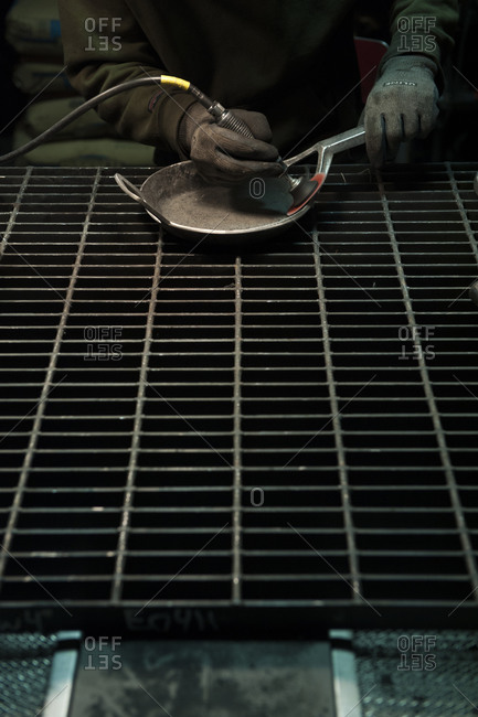 Person finishing a cast iron pan by hand