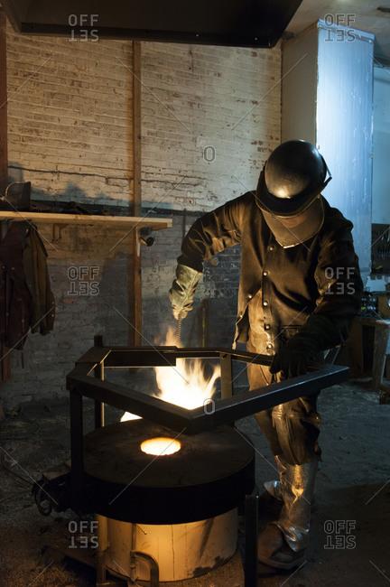 Blacksmith using a kiln in a foundry