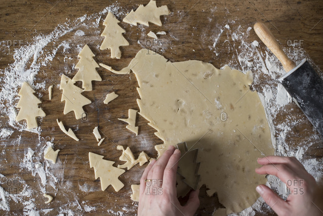 Woman cuts out tree cookies from dough