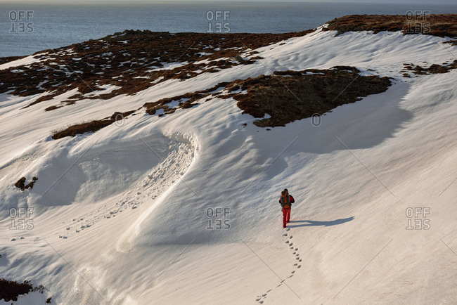 Man hiking snowy Icelandic mountainside