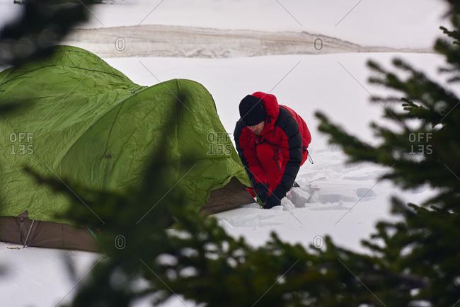 Man preparing campsite in snowy wilderness
