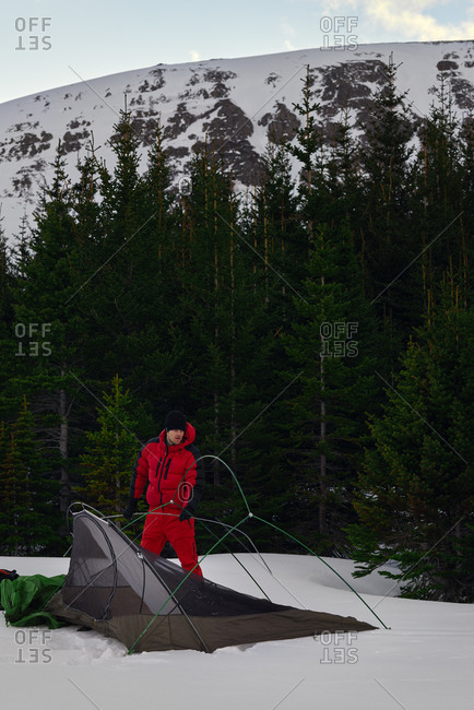 Man setting up tent in snowy wilderness