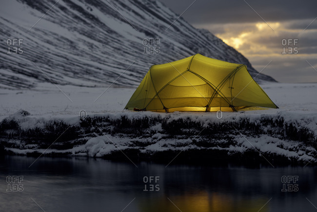 Camp aglow by water in Iceland