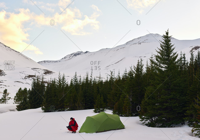 Man by tent in snowy Iceland