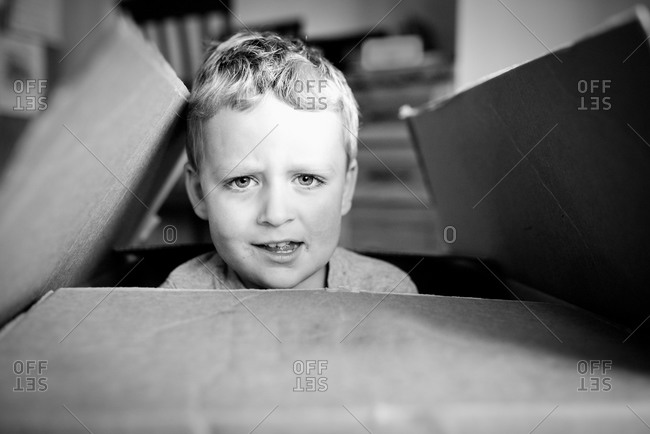 Boy peeking out of a cardboard box