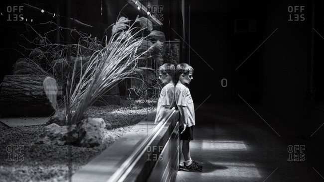 Boy leaning against building at night