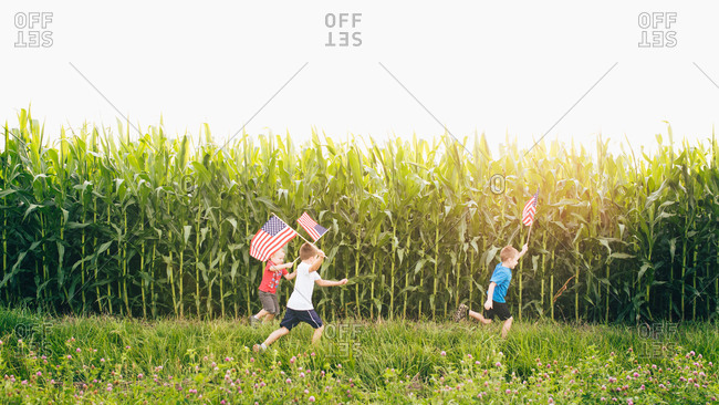 Kids running at a cornfield with American flags
