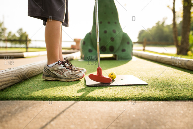 Low section of boy playing mini golf