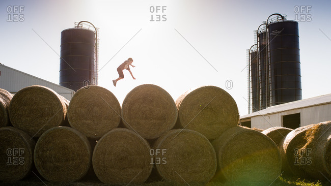 Boy jumping between bales of hay