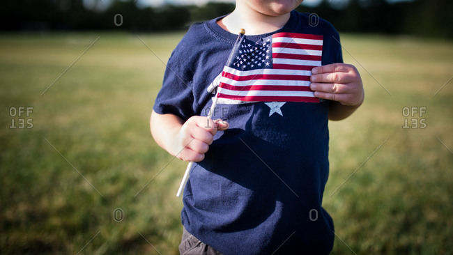 Boy holding American flag to chest
