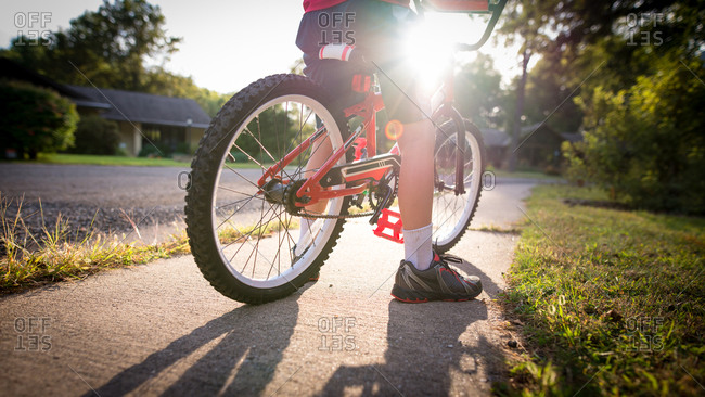 Low section of boy riding bike