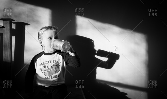 Boy drinking milk in sunlight