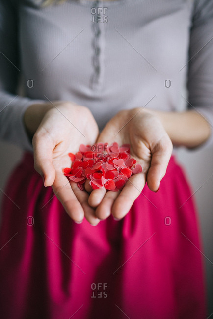 Woman holding tiny hearts in her hands