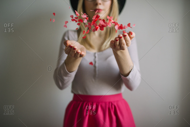Young woman tossing heart shaped confetti