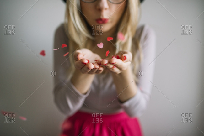 Young woman blowing heart shaped confetti