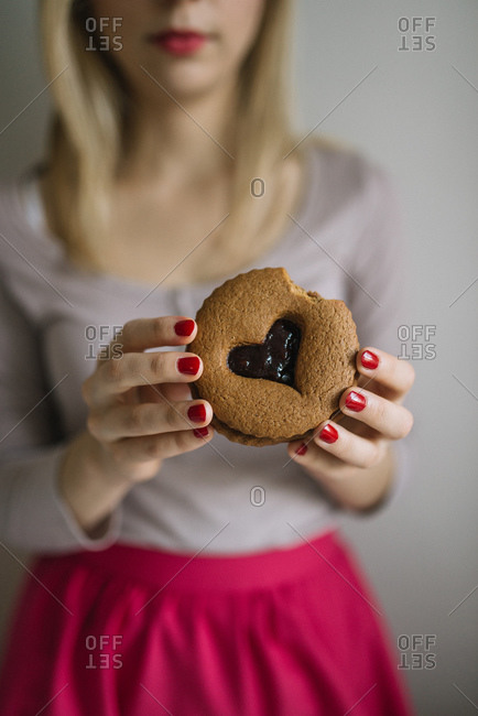 Woman eating a valentine cookie