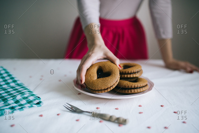 Woman taking a valentine cookie from a plate