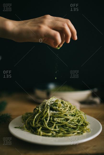Sprinkling parmesan onto pasta with pesto