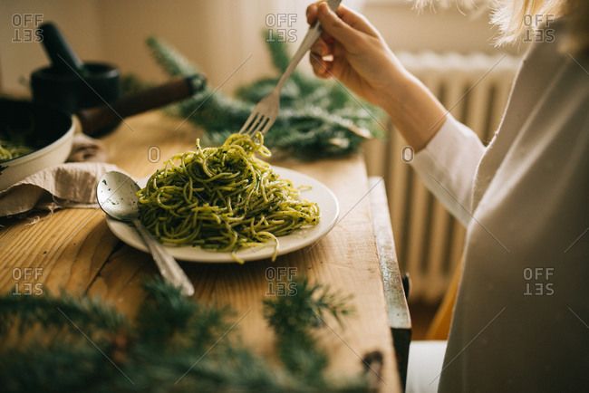 Woman eating spaghetti with pesto