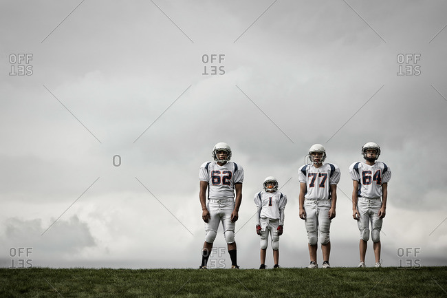 A group of four American football players in sports uniform