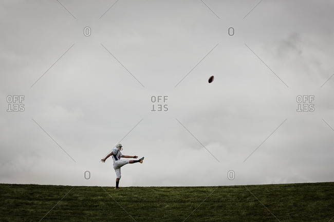 An American football player in uniform, side view, practicing his kicking