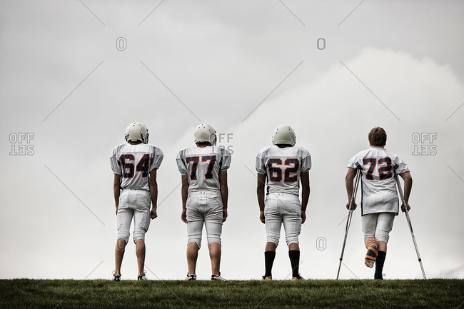 Rear view of a group of four American football players in sports uniform