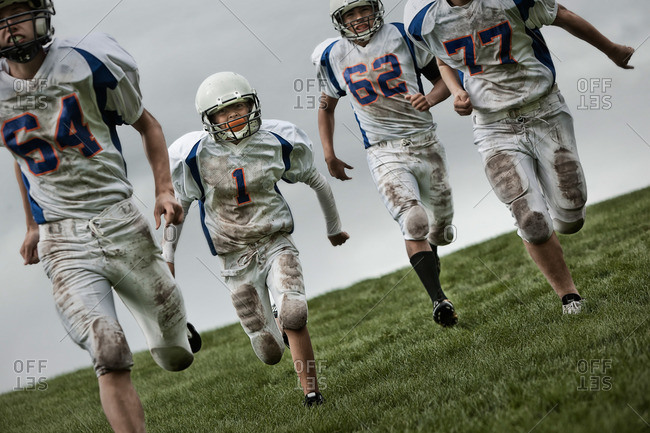 A group of four American football players in sports uniform and protective helmets running forward
