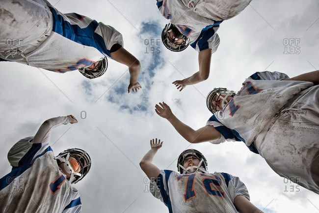 A group of American football players in sports uniform and protective helmets, in a team huddle viewed from below