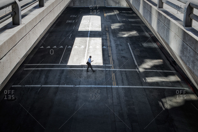 View from above onto a city plaza and man walking from shadow into sunlight