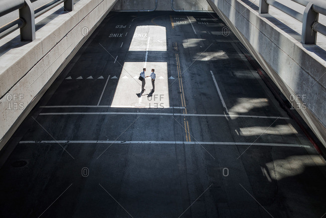 View from above onto a city plaza and two men walking from shadow into sunlight