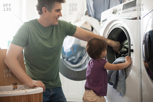 A man and a toddler emptying the laundry from the washing machine
