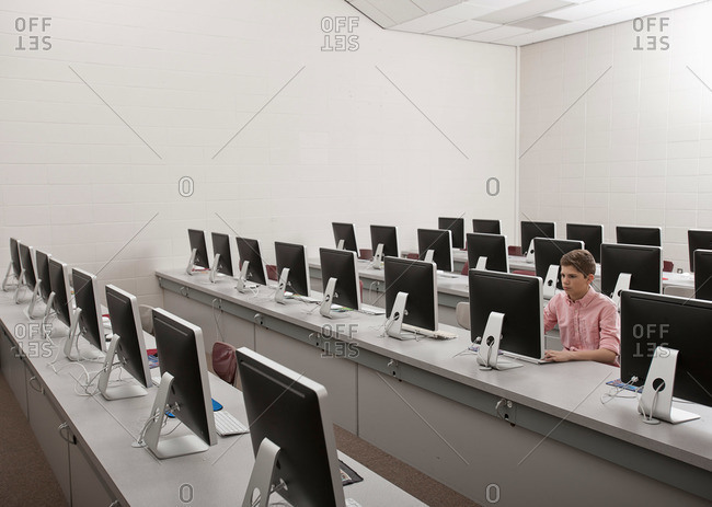 A young man seated working in a computer room