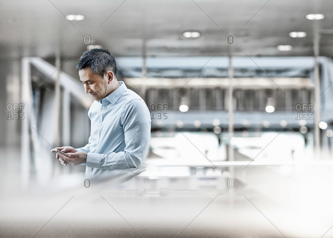 A man standing on a walkway holding his smart phone