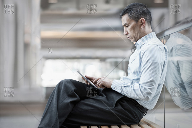 A man sitting using a digital tablet