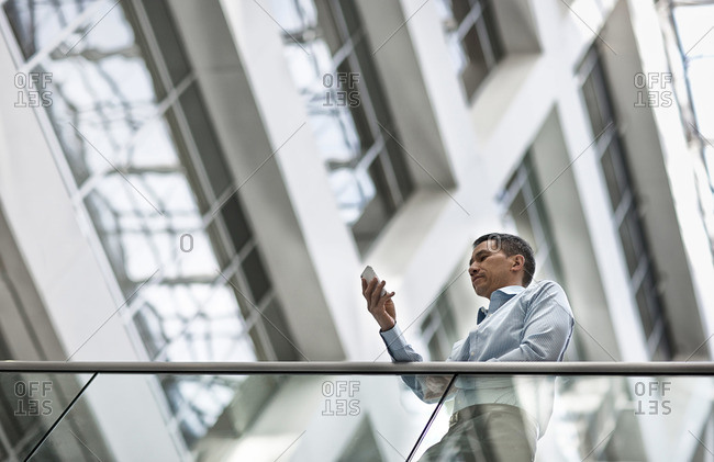 A man checking his smart phone in a large airy building with windows
