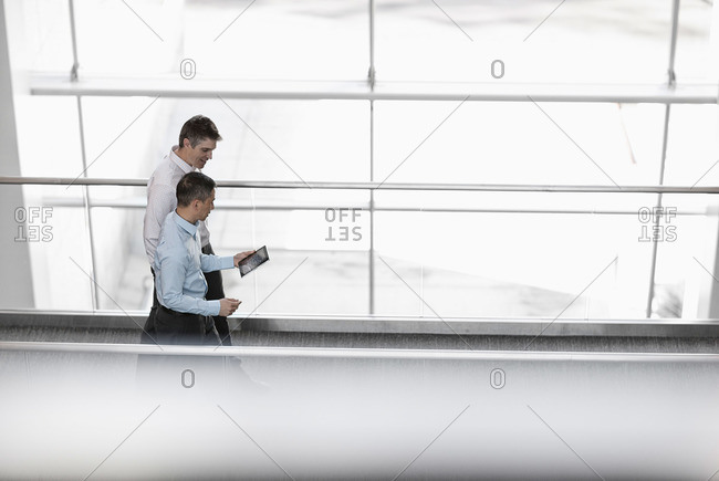 Two men standing by the large windows of a building, looking at the screen of a digital tablet