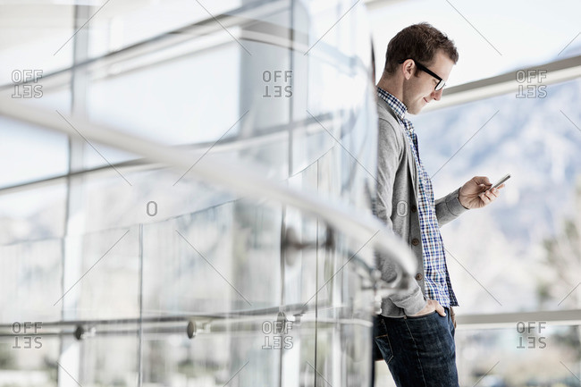 A man standing leaning against a glass panel checking his smart phone