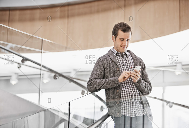 A man standing on spiral stairs checking his smart phone