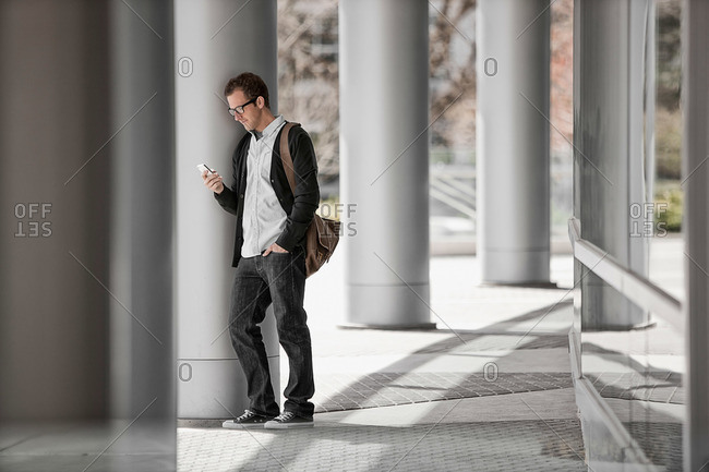 A man outside a building, checking his smart phone